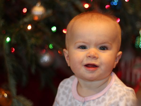 Baby sitting in front of christmas tree
